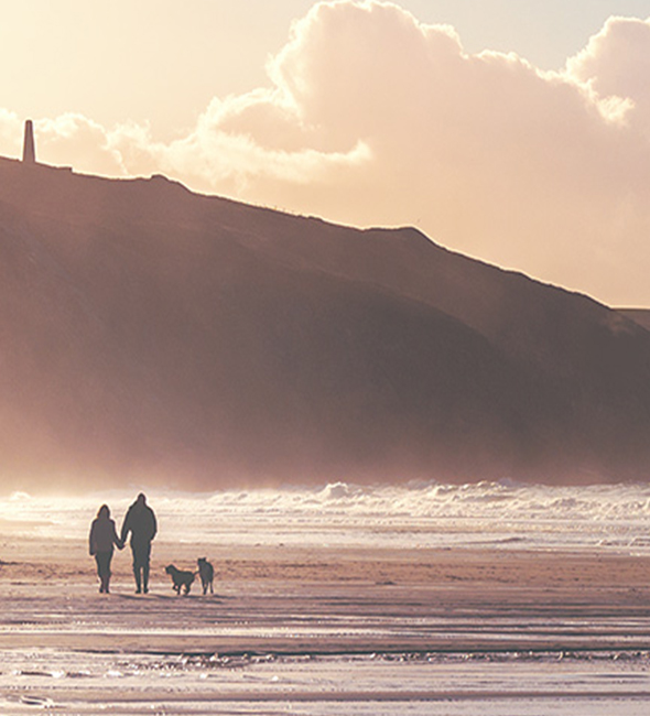 Couple and dog walking on the beach in Cornwall